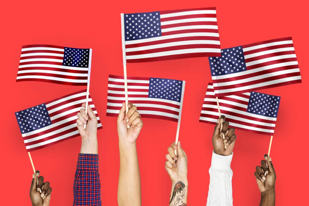 Hands raising up the flag of America.